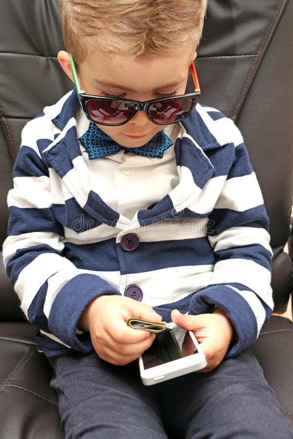 Little boy holding dollar bills. In his hand right and the left draws a phone sitting in royalty free stock images