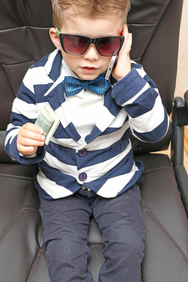Little boy holding dollar bills. Preschool boy sitting in a chair, talking on the phone and holding a cash dollar royalty free stock image