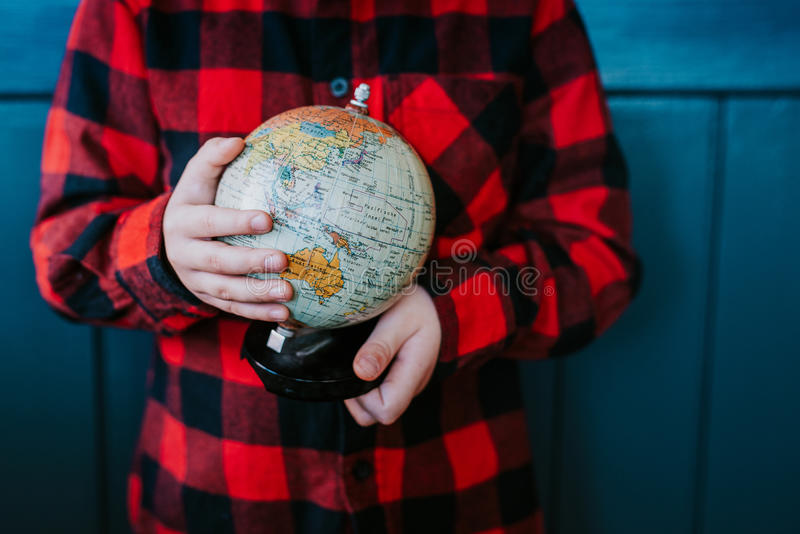 A little boy is holding a globe royalty free stock image
