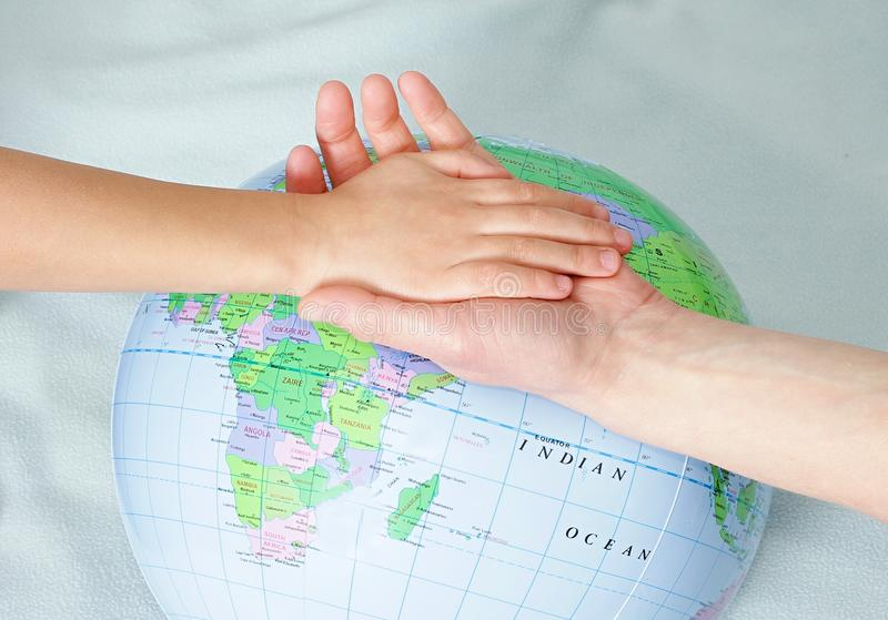 Little boy holding hands with globe in background royalty free stock photography