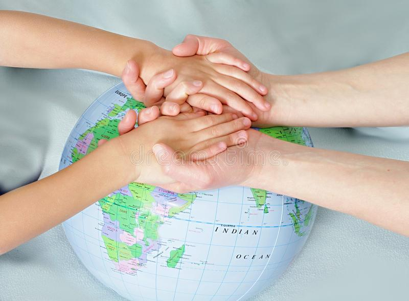 Little boy holding hands with globe in background stock photography