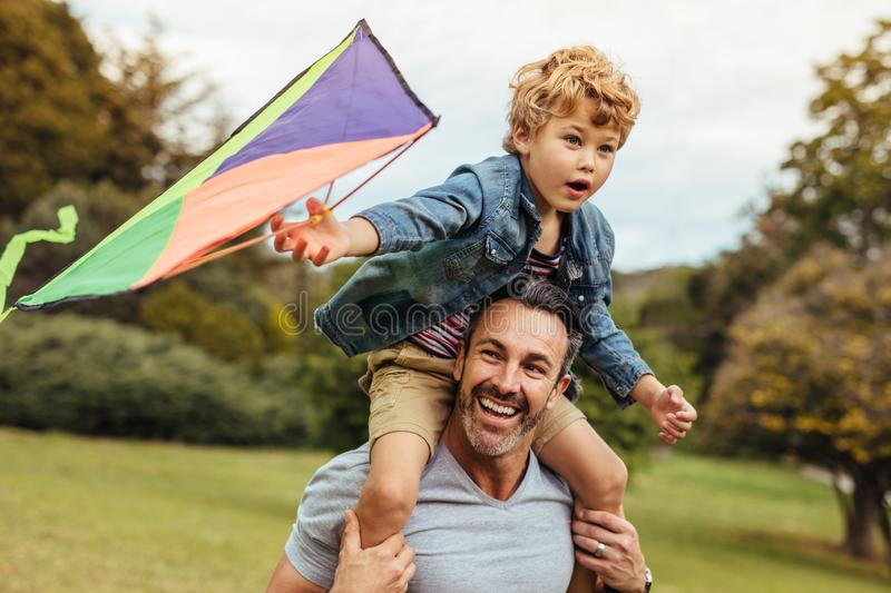 Happy father and son flying kite outdoors royalty free stock image