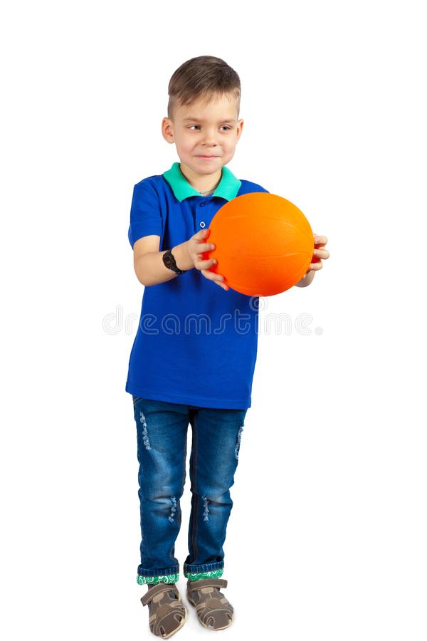 The little boy is holding out the ball stock photos