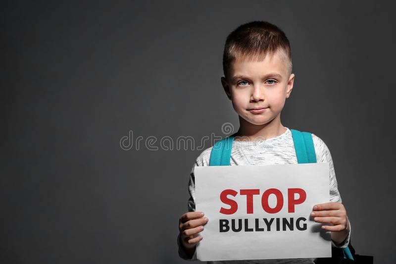 Little boy holding paper with text STOP BULLYING. On dark background stock image