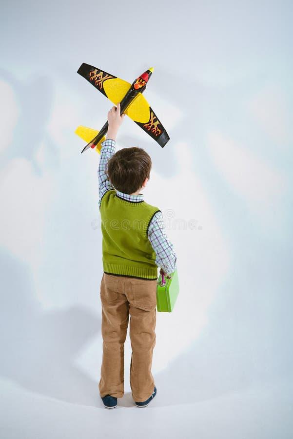 Little boy holding a plane model and handbag royalty free stock image