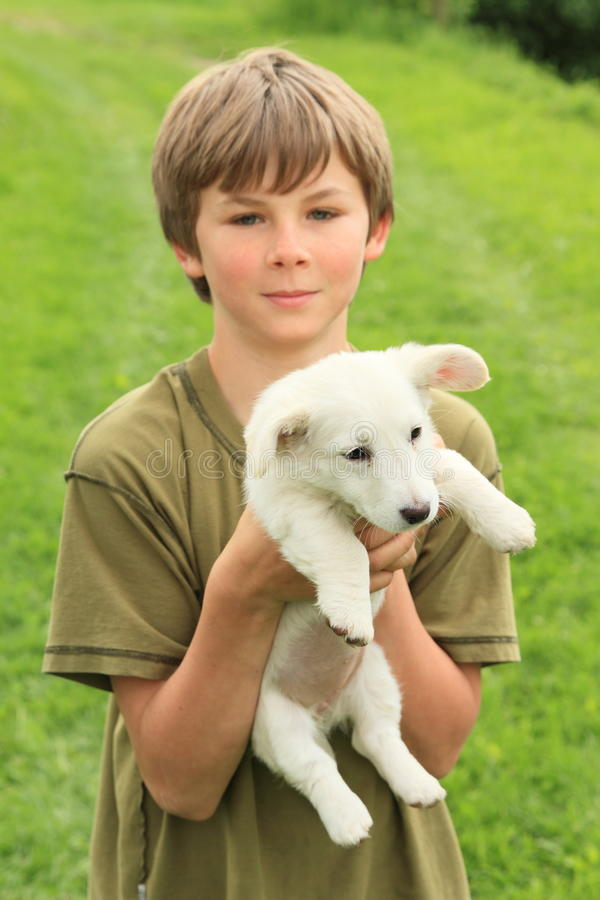 Little boy holding a puppy. Smiling little boy holding white puppy stock image
