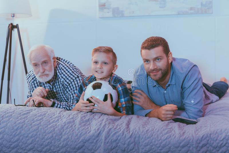 Little boy holding soccer ball, his father and grandfather lying on bed together and watching stock photo