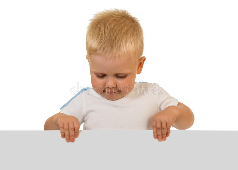A little boy holding with two hands blank banner isolated on white stock image