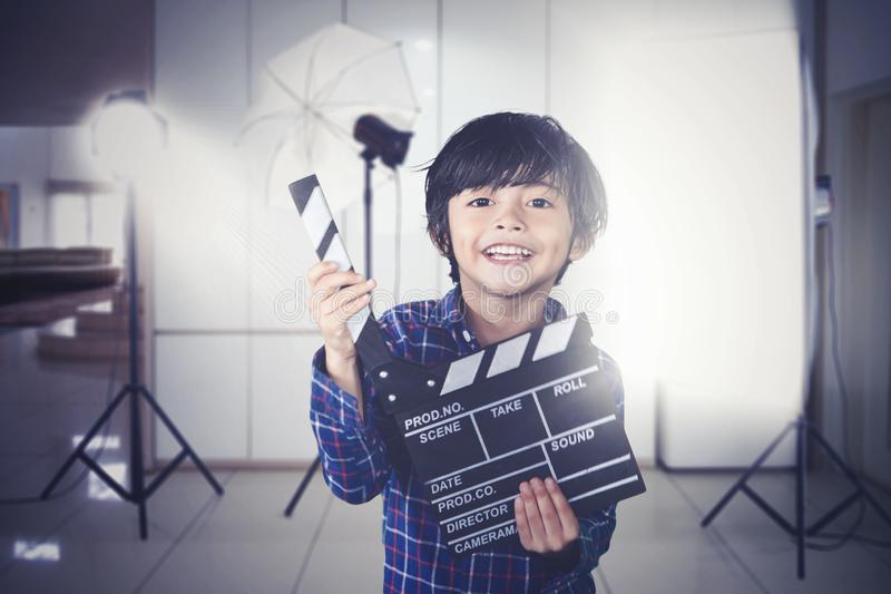 Little boy holds clapperboard during film production. Picture of a little boy looks happy while holding clapperboard during the film production royalty free stock image