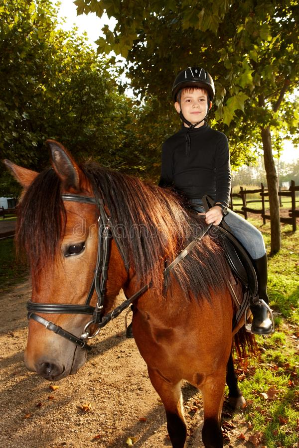 Little boy horseback riding in the green. Cute little boy horseback riding in the green at autumn royalty free stock images