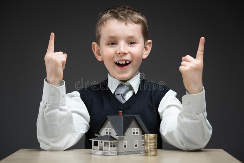 Little boy with house model and pile of coins. Portrait of little boy with house model and pile of coins on grey background. Concept of real estate and royalty free stock image