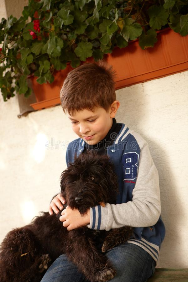 Little boy hugging dog. Little boy sitting outdoors hugging black dog royalty free stock photography