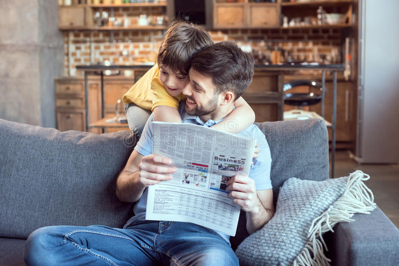 Little boy hugging father reading newspaper at home stock photo