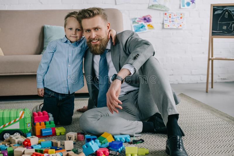 Little boy hugging smiling father in business suit at home work and life. Balance concept royalty free stock photos