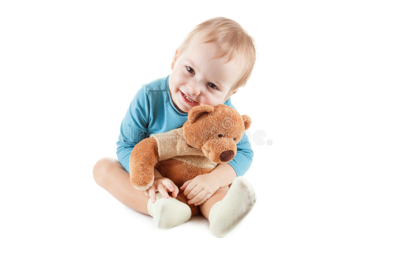 Little boy hugging a teddy bear on white background. Little boy hugging a teddy bear isolated on a white background royalty free stock photography