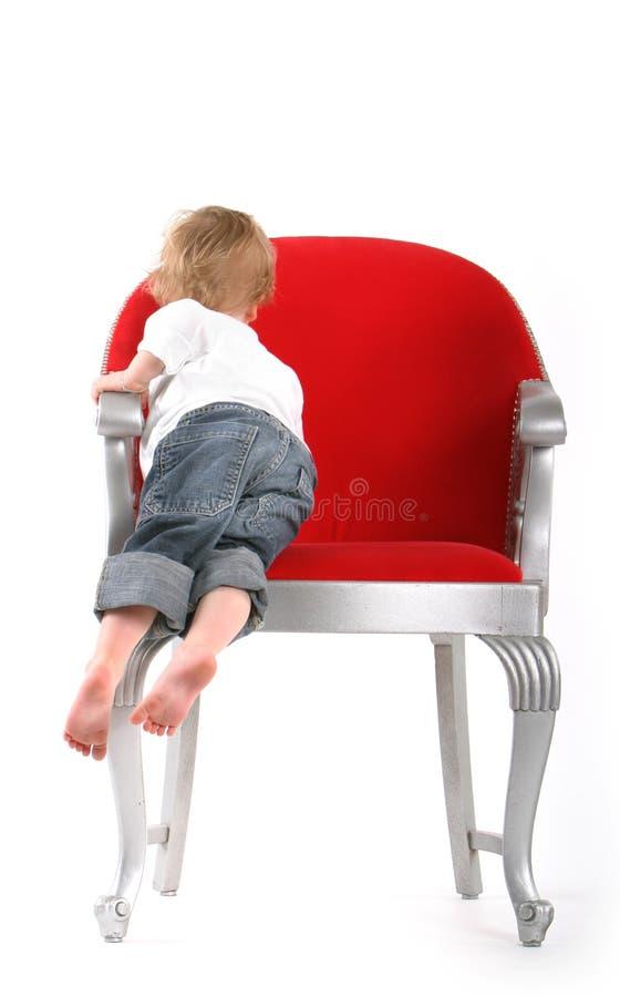Little Boy im Großen roten Stuhl lizenzfreie stockbilder