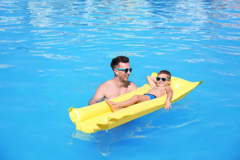 Little boy on inflatable mattress with father royalty free stock image