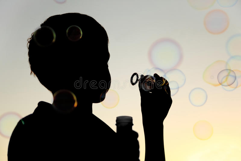 Little boy inflating many soap bubbles royalty free stock photo
