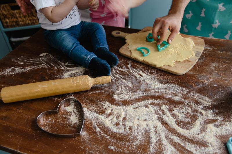 Little boy in jeans mixing flour in the kitchen on a table making some mess stock images