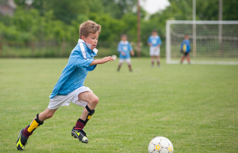 Little Boy jouant au football image stock