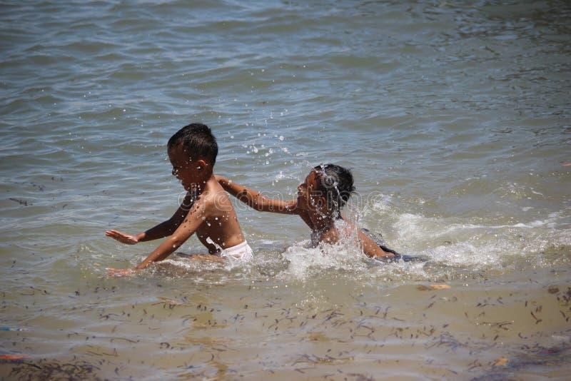 Little Boy jouant sur la plage de Bama, parc national de Baluran image stock