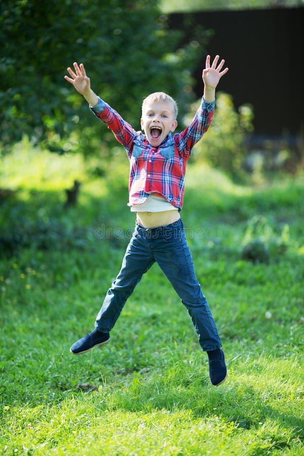 Little boy joyfully jumping in the summer. In the garden royalty free stock photo