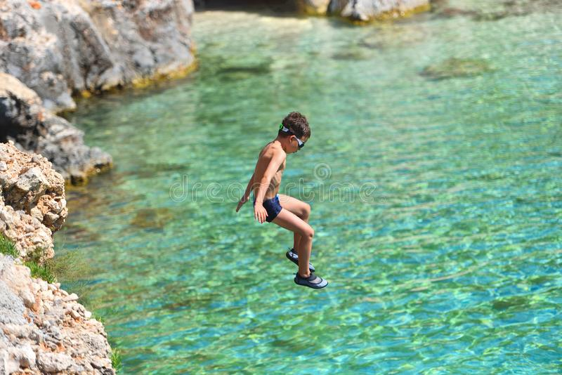 Little boy jumping off cliff into the ocean. Summer fun lifestyle. Brave kid stock photography