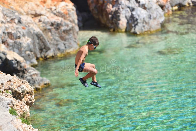 Little boy jumping off cliff into the ocean. Summer fun lifestyle. Brave kid stock photos