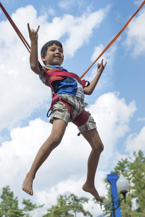 A little boy is jumping on a trampoline in the park. He soars in the air against the blue sky and shows a gesture that he is stock image