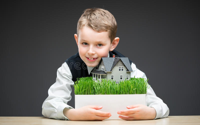 Little boy keeping house model. Portrait of little boy keeping house model on grey background. Concept of real estate and deal stock photography