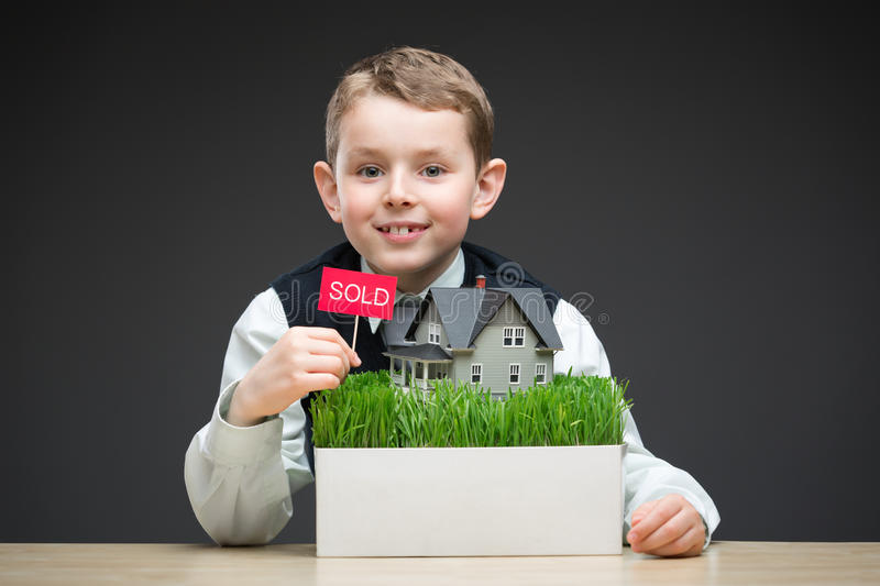 Little boy keeping house model and sold tablet. Portrait of little boy keeping house model and sold tablet on grey background. Concept of real estate and deal stock images