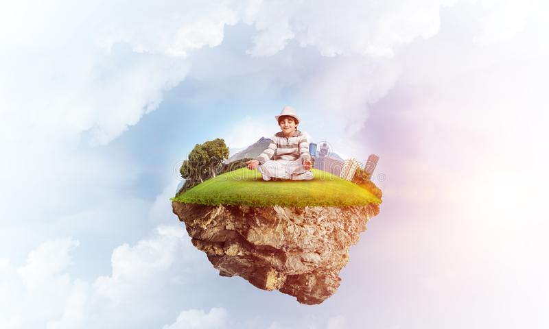 Little boy keeping mind conscious. Young little boy keeping eyes closed and looking concentrated while meditating on flying island in the air with cloudy vector illustration