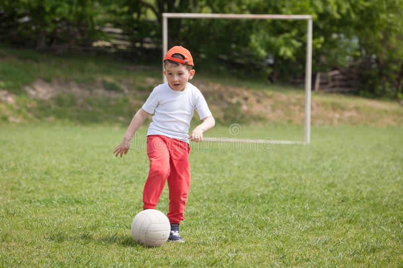 Little boy kicking ball in the park. playing soccer football in the park. Sports for exercise and activity royalty free stock photo