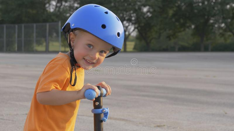 Little boy kid, child in orange t-shirt and blue helmet is riding scooter. Childhood memories, safe and funny experience . Closeup portrait, summer, sunny royalty free stock photography