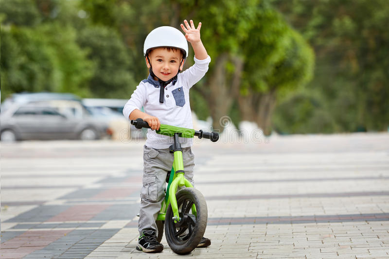 Little boy kid in helmet ride a bike in city park. Cheerful child outdoor. Happy childhood concept royalty free stock images