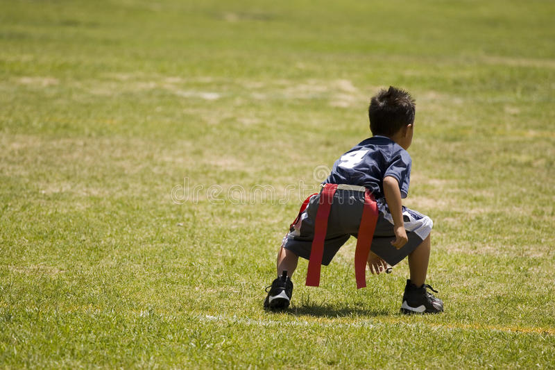 Little boy kid playing flag football on an open field. royalty free stock photography