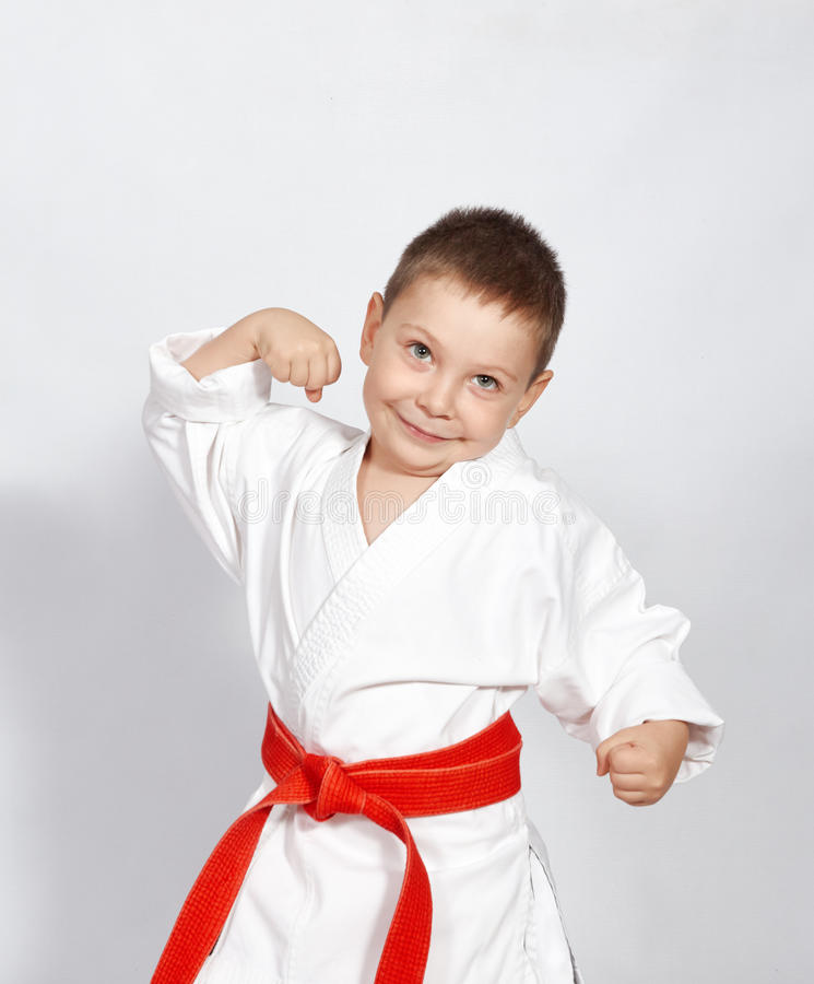 Little boy in a kimono with a red belt and shows his strength. Boy in a kimono with a red belt and shows his strength stock photography