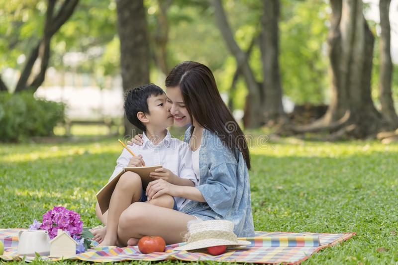 Little boy kiss her mom. Happy asian family having fun outside and sitting picnic in the park stock photography