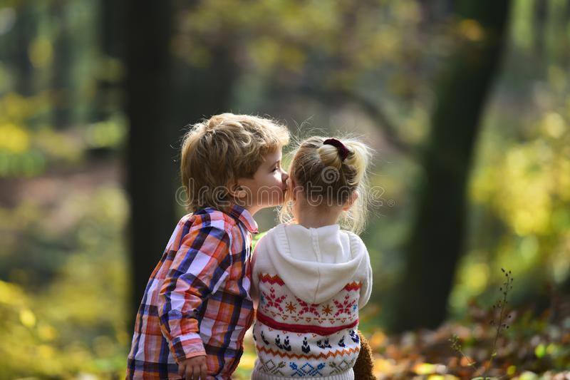 Little boy kiss small girl friend in autumn forest. Brother kiss sister with love in woods. Valentines day concept stock photography