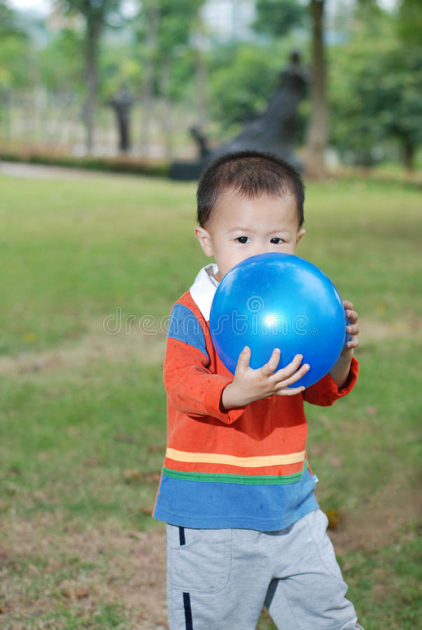 Little boy kissing the balloon. On the lawn stock images