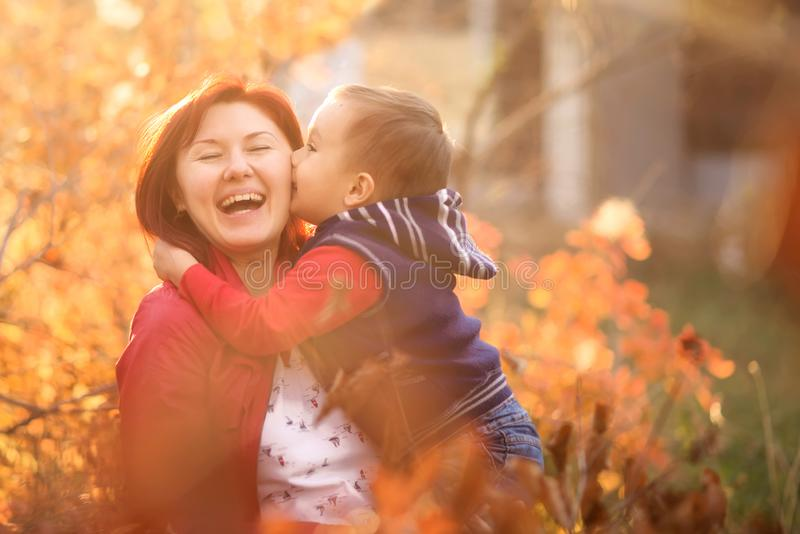Little boy kissing mom in autumn park or garden. Woman is laughing happily. Family reunion concept royalty free stock photo