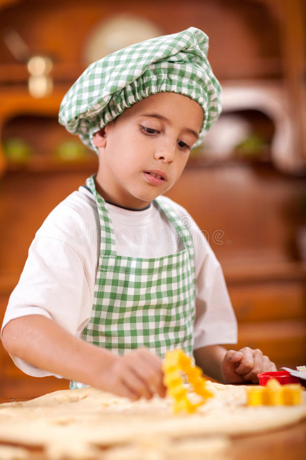 Little boy kneading a dough to make cakes in the kitchen royalty free stock images