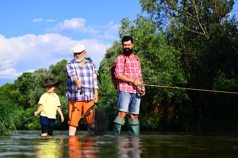 Little boy on a lake with his father and grandfather. Happy fisherman with fishing rod. 3 men fishing on river in summer stock photo