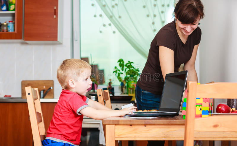 Little boy with laptop and mother cleaning stock images