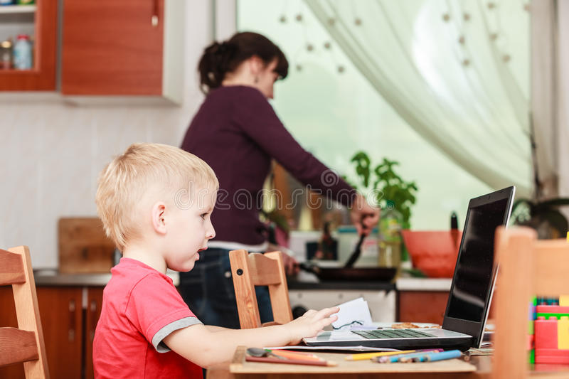 Little boy with laptop and mother cooking in kitchen. Technology and early education. Spending time with family eat together. Child use laptop for fun and stock images