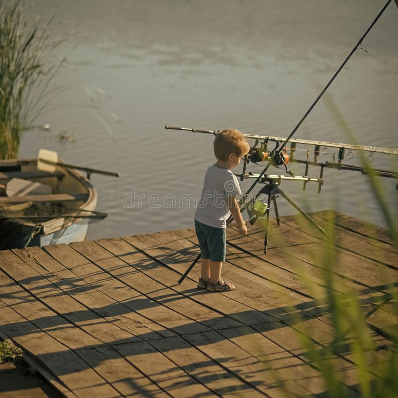 Little boy learn to catch fish in lake or river. Child with fishing rod on wooden pier. Summer vacation, hobby, lifestyle. Childhood, education, training royalty free stock photography