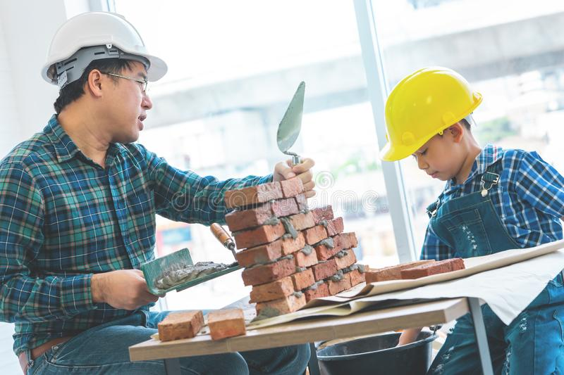 Little boy learning how to build brick wall from his construction father royalty free stock photos
