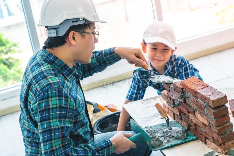 Little boy learning how to build brick wall from his construction father. Little Boy is learning to work on brickwall and be a builder from his craftman father stock images