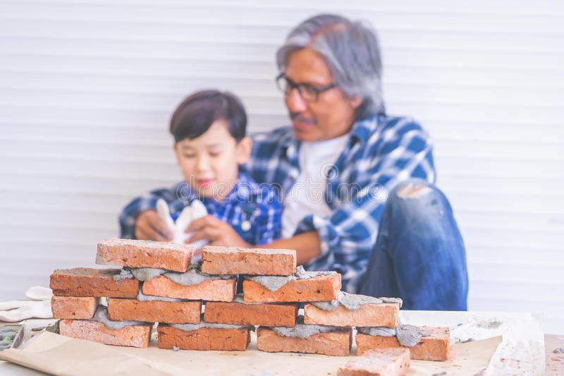 Little boy learning how to construct brick wall from his builder father for family profession future education concept stock photos