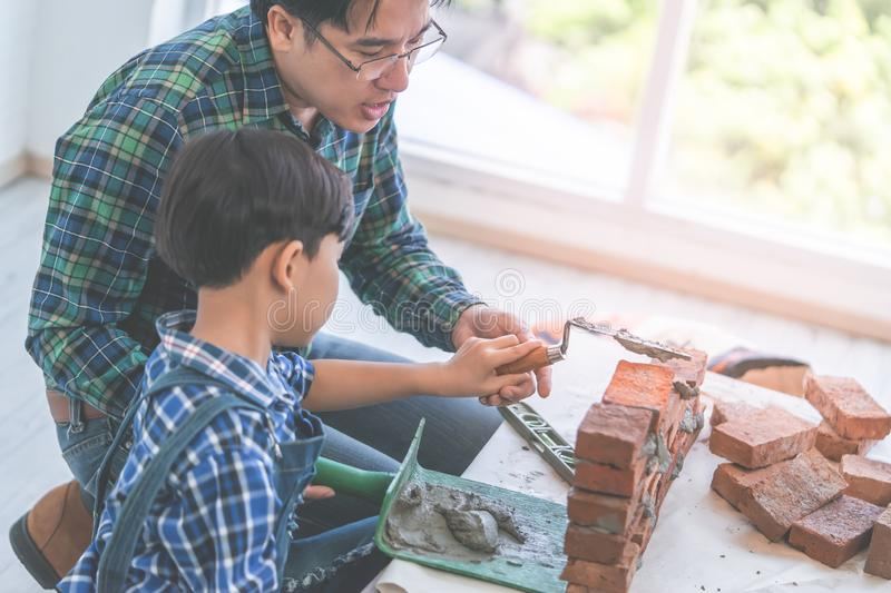 Little boy learning how to lay down brick work from his builder father royalty free stock photography